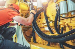 Caucasian Professional Mechanic Fixing Bulldozer Engine Inside Heavy Equipment Repair Shop - article illustration