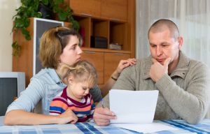 Trammell Piazza Law Firm article illustration worried man, wife and child at table looking at paperwork - worker injuries emotional financial impact on families