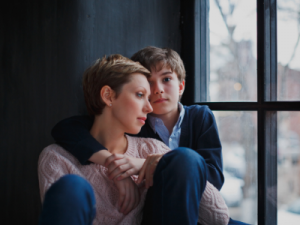 worried mom being comforted by son sitting in window - article illustration